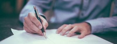 Homem a assinar documento com caneta